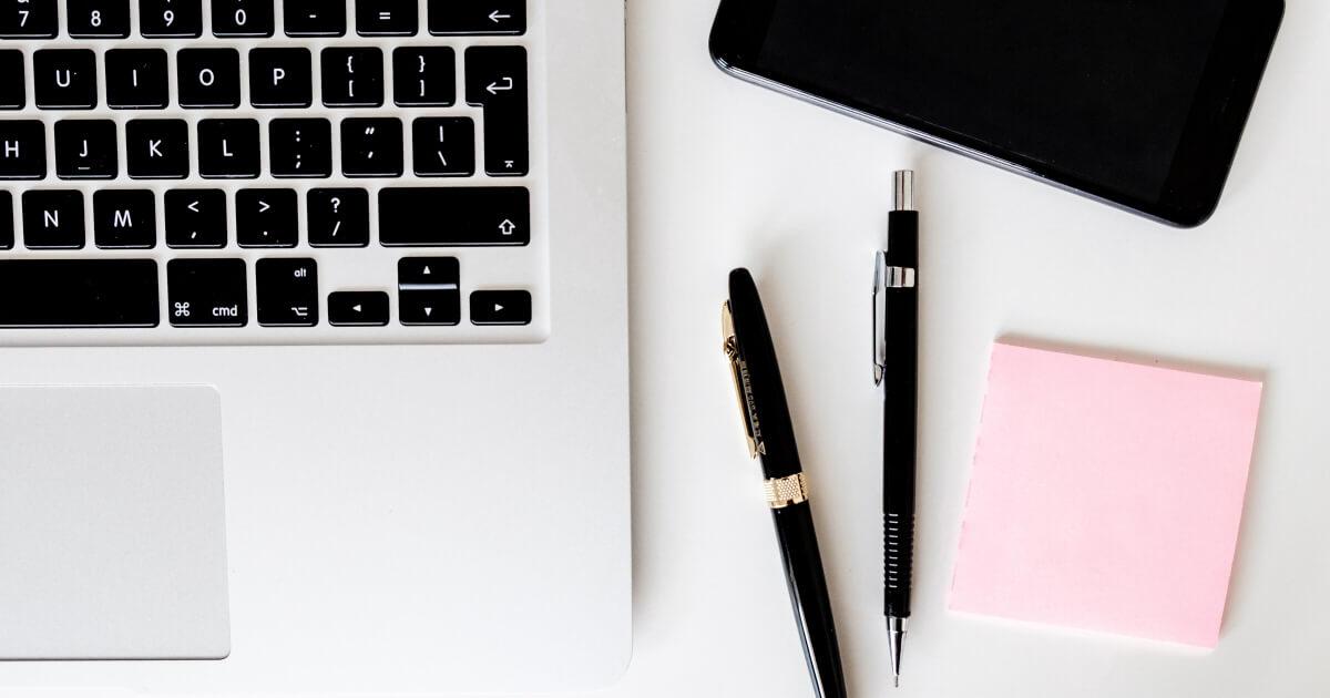 パソコンとペンとメモ用紙の画像